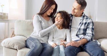 Homem e mulher sentados em sofá. Entre eles, uma menina está sentada. A mulher tem sua mão direita no rosto da menina e elas se olham. O homem observa as duas. Todos sorriem.