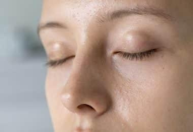 Imagem ampliada de uma mulher de olhos fechados.