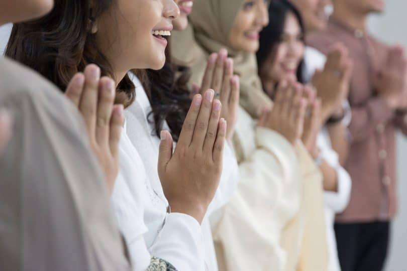 Grupo de pessoas de diferentes religiões lao a lado, rezando