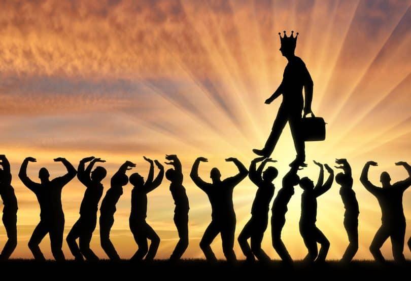 Imagem de um homem usando uma coroa enquanto caminha sobre várias pessoas em pé.