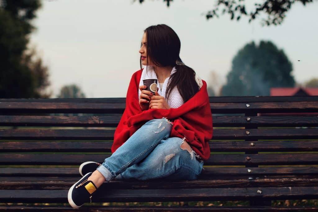 Mulher sentada em um banco de madeira segurando um copo de café e olhando para o lado