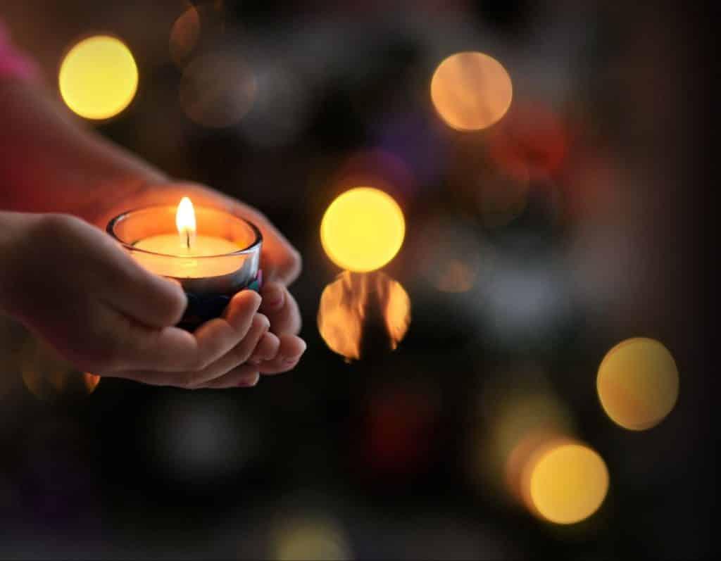 Mãos segurando uma vela acesa.