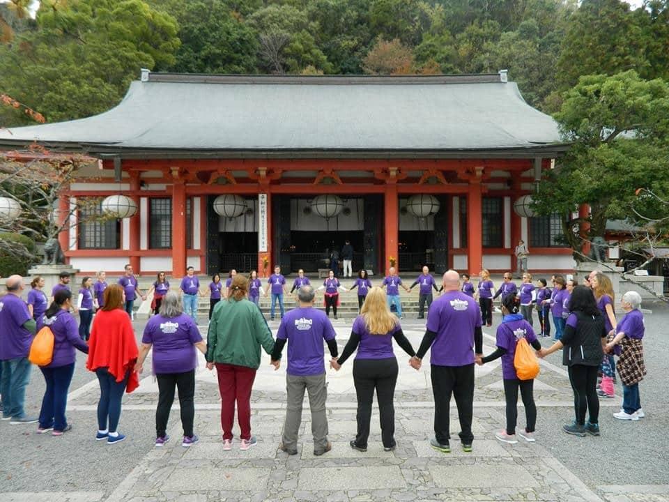 Grupo de pessoas de mãos dada, formando um círculo, em frente a um templo japonês.