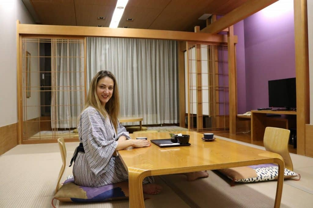 Mulher sentada em almofada no chão, em frente a uma mesa de madeira baixa, com xícaras de chá.