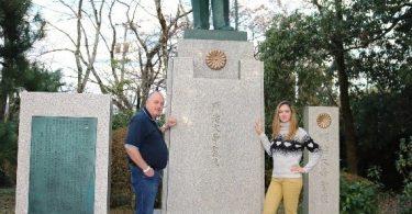 Um homem e uma mulher ao lado de uma estátua de um homem, com pedestal alto.