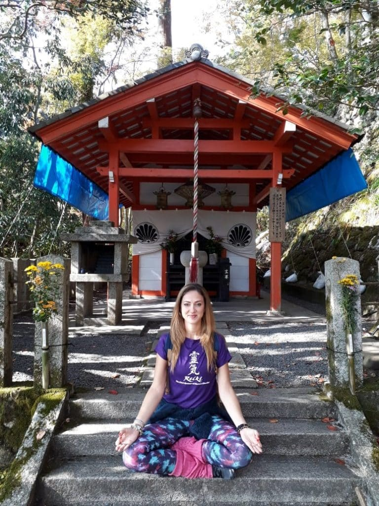 Mulher sentada com as pernas cruzadas em escada, em frente a um pequeno templo.