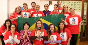 Grupo de pessoas com camisetas vermelhas, segurando uma bandeira do Brasil.
