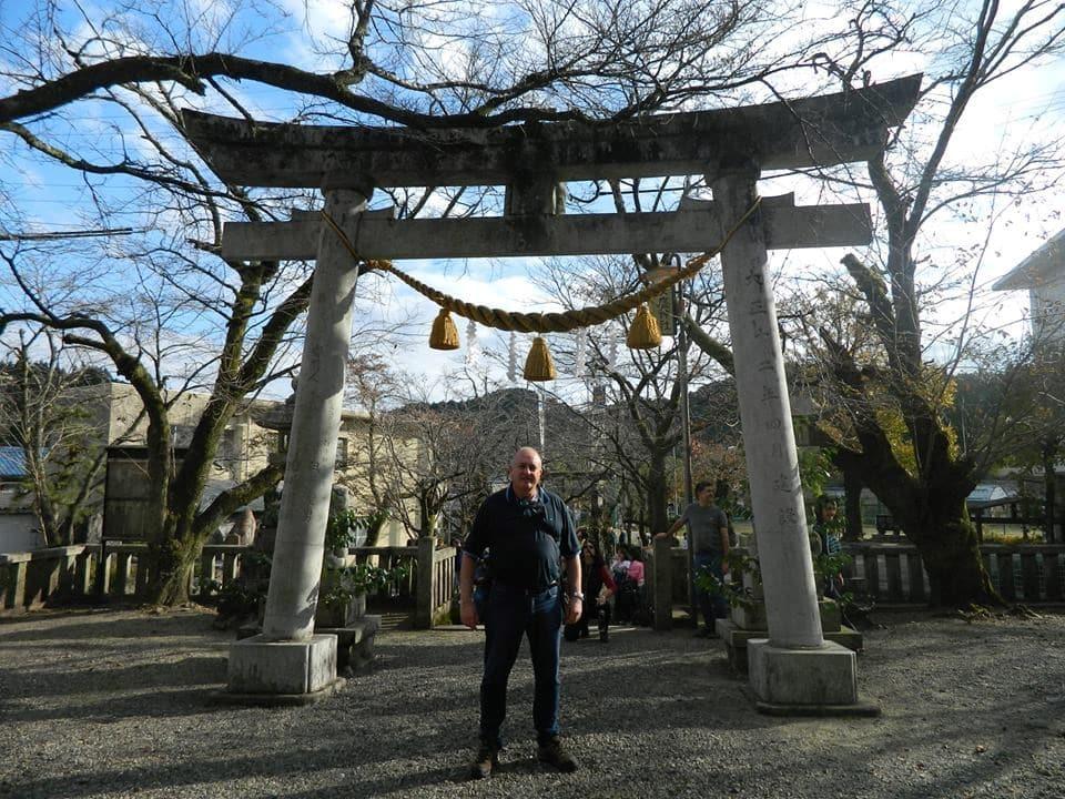Homem de pé em frente a portal de templo japonês.