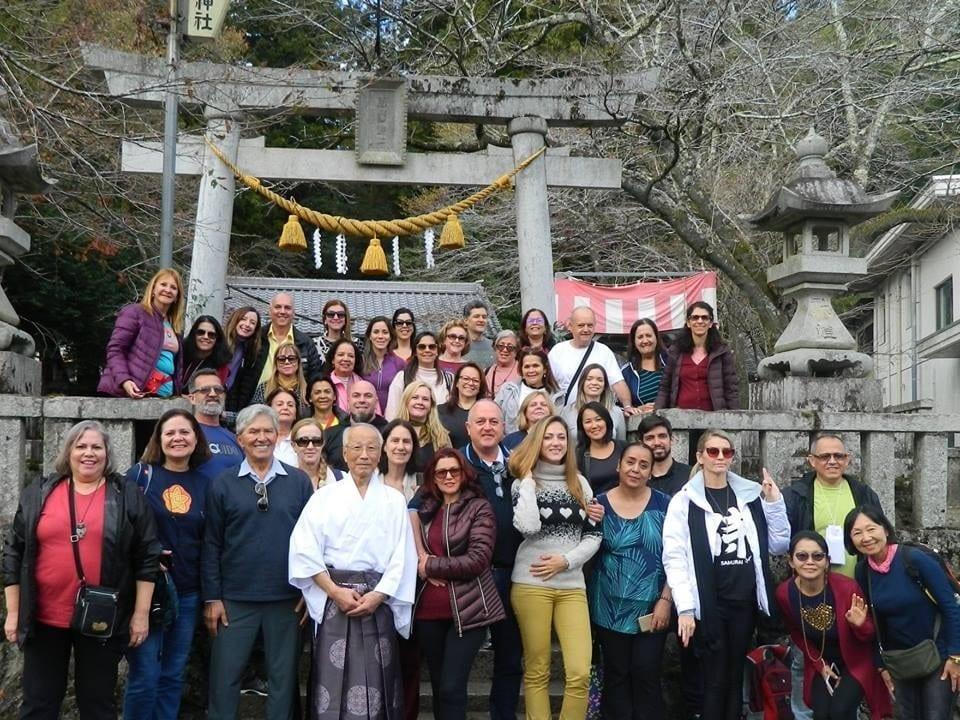 Grupo de pessoas posando para foto em frente a um templo.