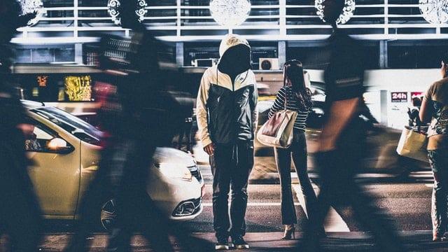 Pessoa parada na rua com outras pessoas em movimento ao lado