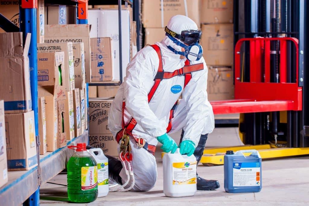 Pessoa trabalhando com equipamentos de proteção pessoal enquanto manuseia embalagens de produtos químicos.