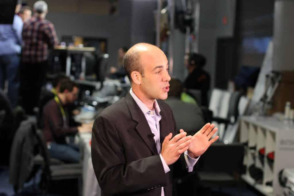 Homem falando, com microfone de lapela e gesticulando com as mãos.