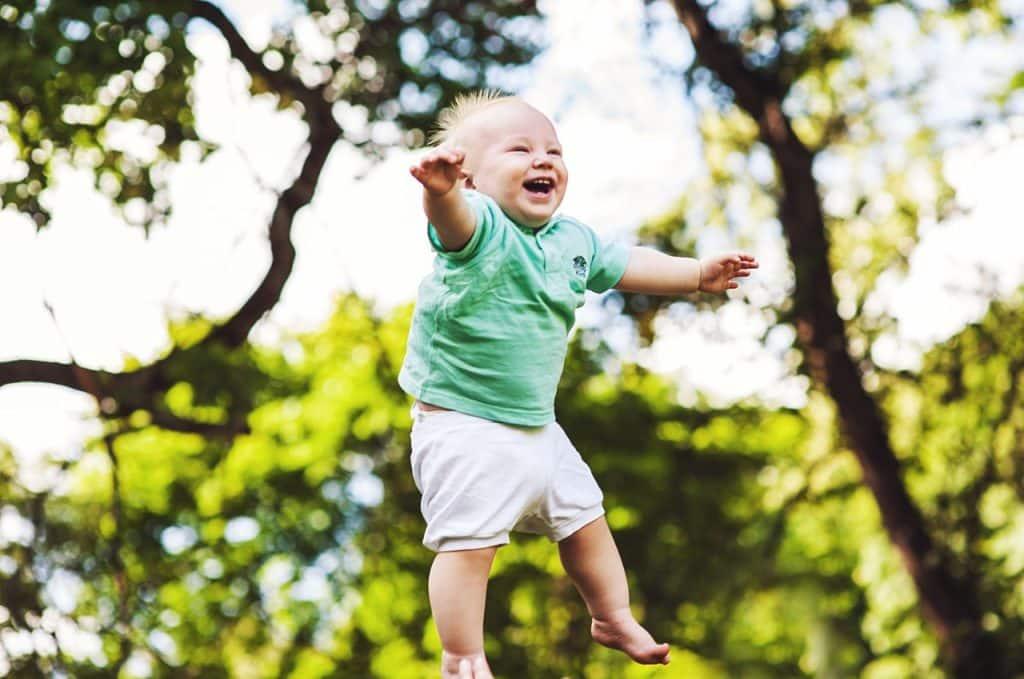 Bebê no ar depois de ser jogado, rindo e com os braços abertos.