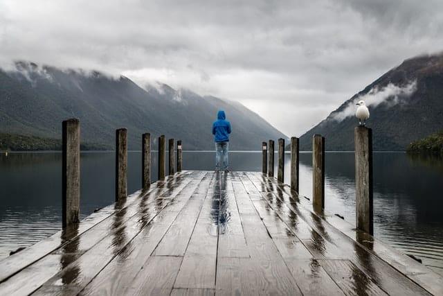 Homem em pé em deck de madeira de costas com montanhas ao fundo