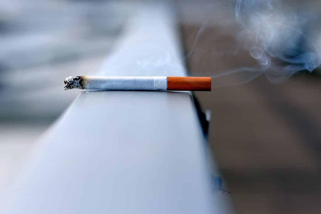 Cigarro aceso sobre um muro.