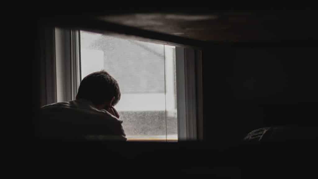 Pessoa apoiada em uma janela em um quarto escuro