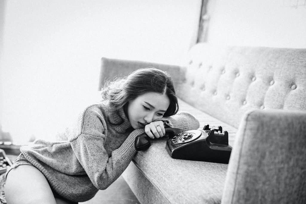 Mulher sentada no chão segurando telefone no sofá