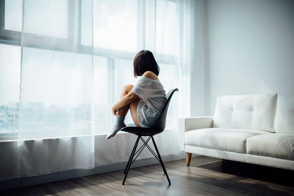 Menina sentada em uma cadeira na sala, olhando pela janela.