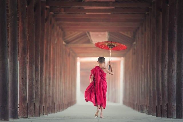 Menino buda andando em templo de costas
