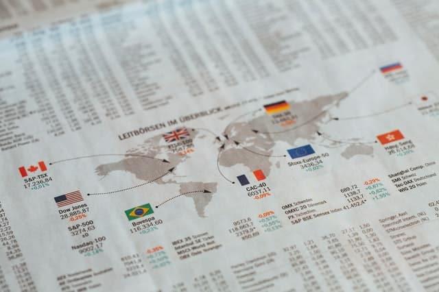 Folha com mapa mundi e bandeiras de países com valores comerciais