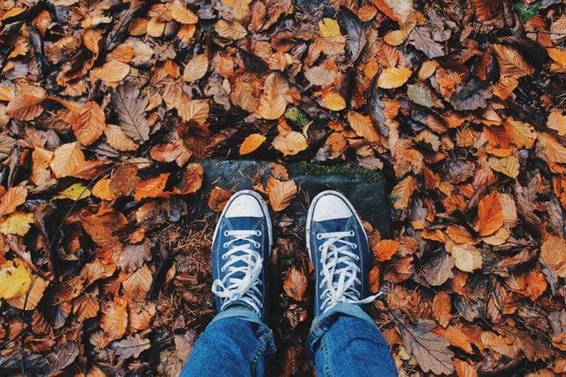 Pés com tênis visto de cima pisando em folhas de outono