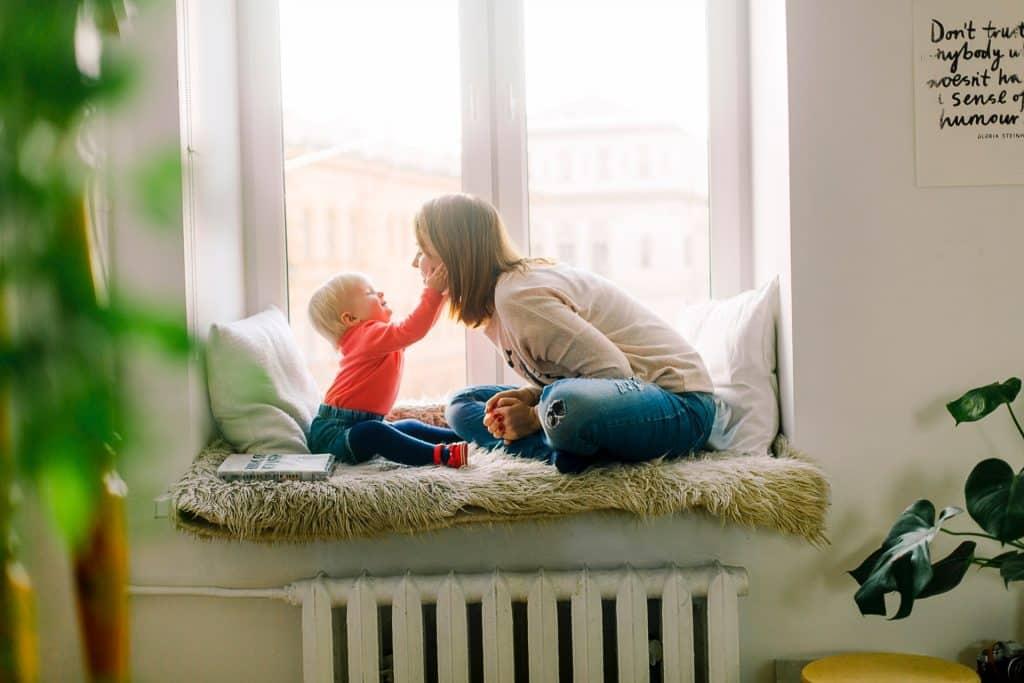 Bebê sentado na frente de uma mulher. A mulher está inclinada para frente em direção ao bebê, que encosta uma de suas mãos na bochecha da mulher.