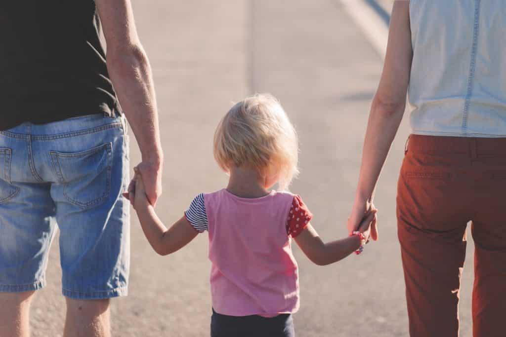 Criança pequena andando de mãos dadas com um homem e uma mulher. A criança está no centro, e todos estão de costas para a câmera.