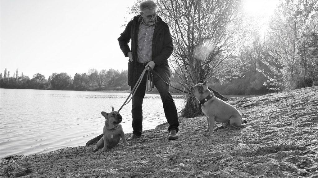 Imagem em preto e branco de um homem em um lago segurando em suas duas guias com os seus cachorros de estimação.