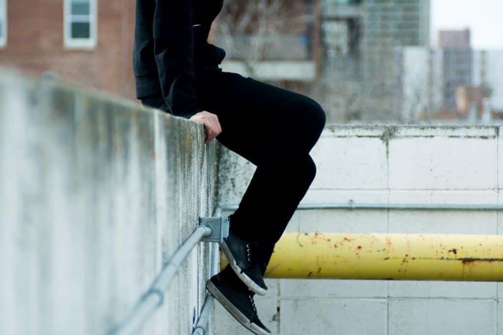 Pessoa sentada em um muro antigo, na cidade.