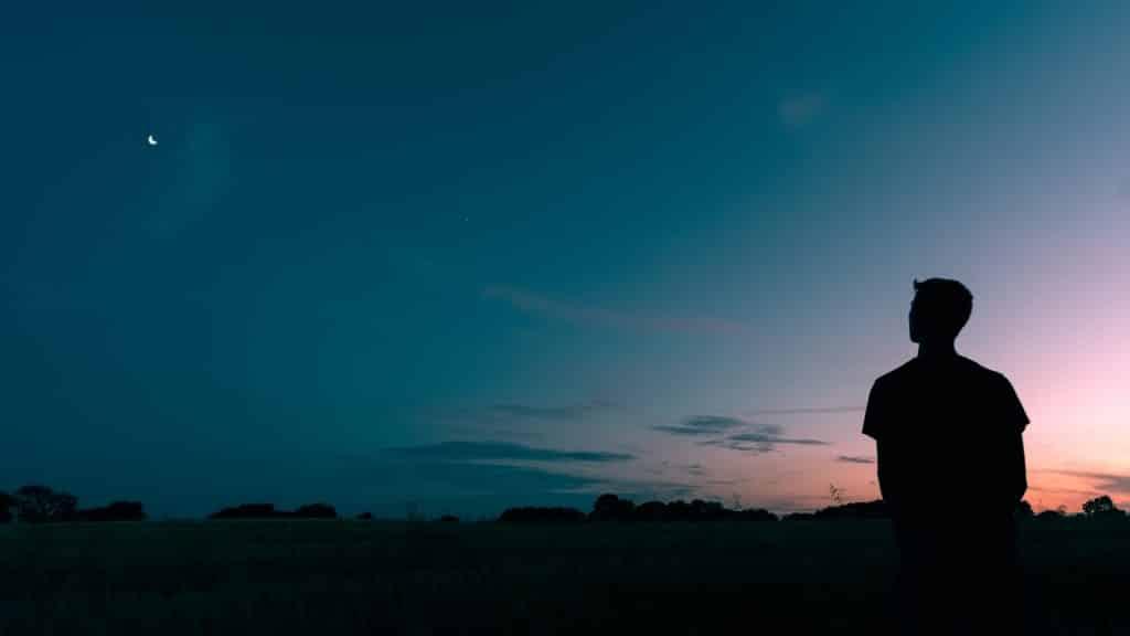 Silhueta de um homem olhando para a natureza a noite