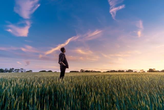 Homem em pé em campo verde com céu azul e algumas nuvens refletindo