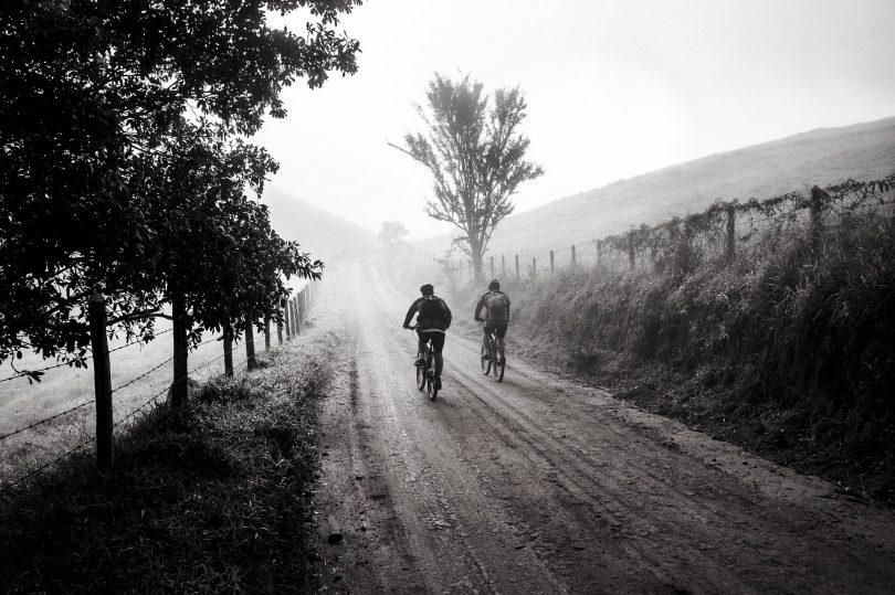 Imagem em preto e branco de uma estrada com um casal de amigos andando sobre ela de bicicleta.
