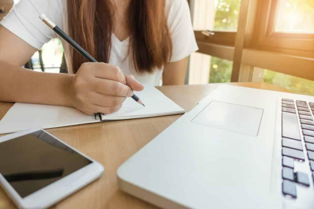 Mulher escrevendo com lápis em um caderno, com um celular ao lado e um notebook em sua frente.