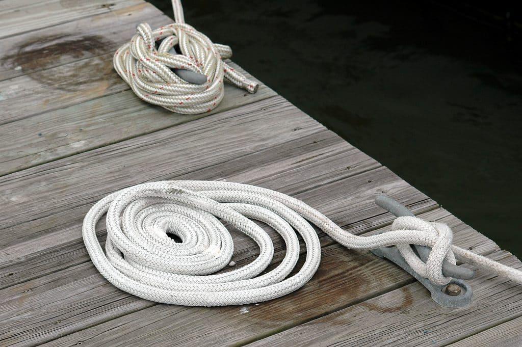 Imagem de duas cordas de nylon, sendo uma na cor branca e a outra na cor bege com traçado vemelho Elas estão sobre o pier e ambas estão com nós.