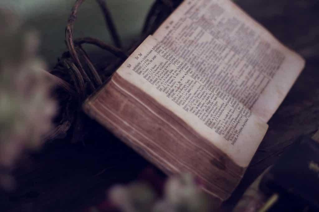 Imagem em preto e branco de uma bíblia antiga aberta.