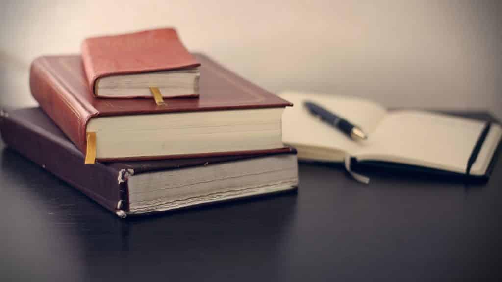 Imagem de três livros espíritas fechados um sobre o outro. O primeiro livro é o menor de todos.  Eles estão dispostos sobre ume mesa preta. Ao lado um caderno de anotações e uma caneta sobre ele.