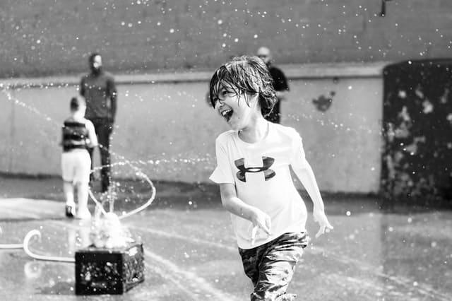 Garoto correndo feliz com água em volta em preto e branco