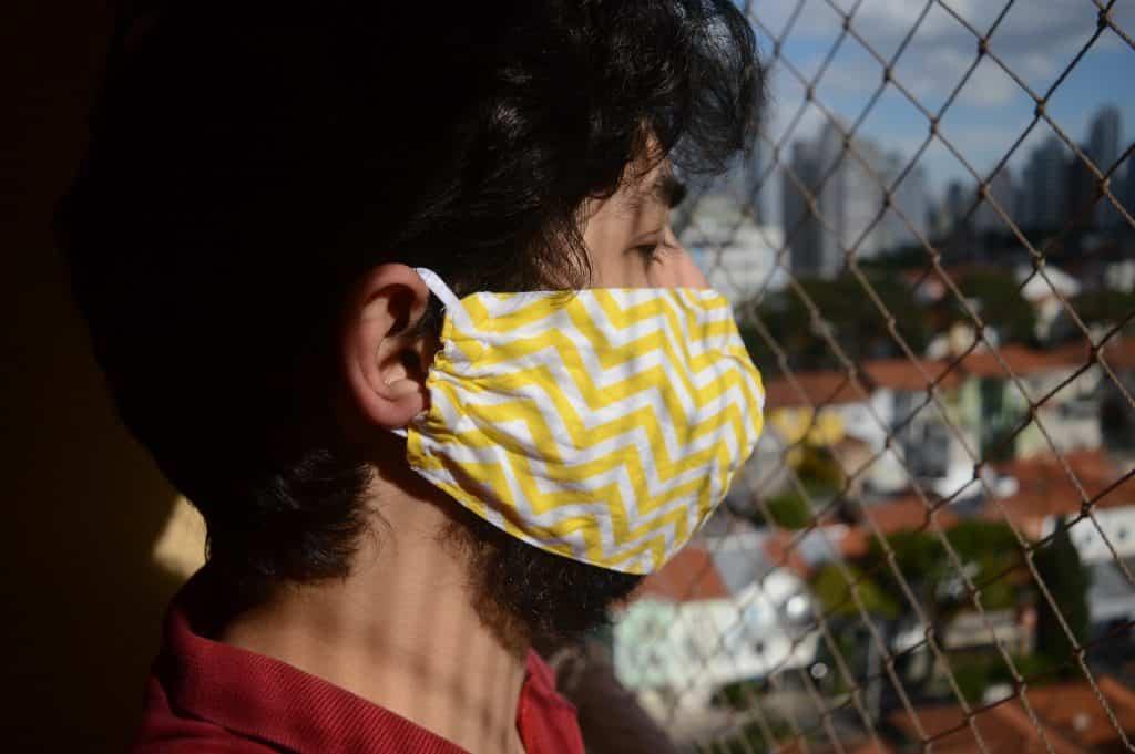 Homem usando mascara de proteção ao lado de uma grade