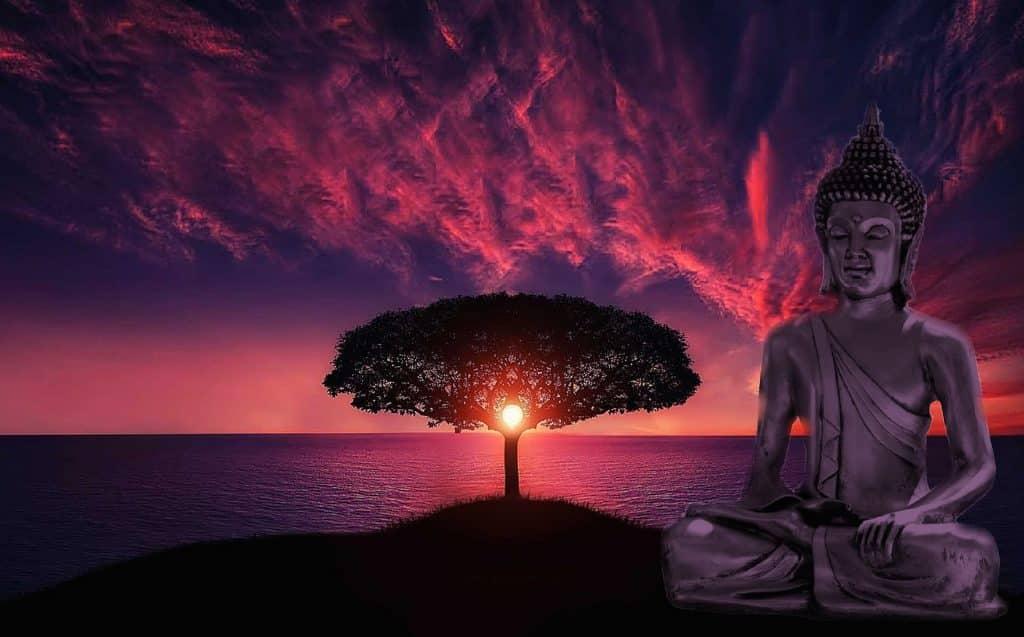 Imagem de Buda em posição de meditação. Ao fundo temos um lago, uma árvore com copa bem frondosa e um lindo por do sol.