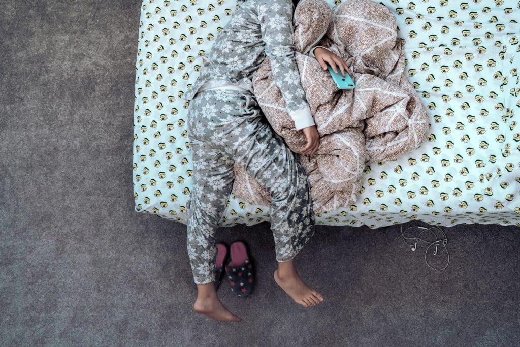 Mulher deitada na cama enrolada na coberta e segurando seu celular