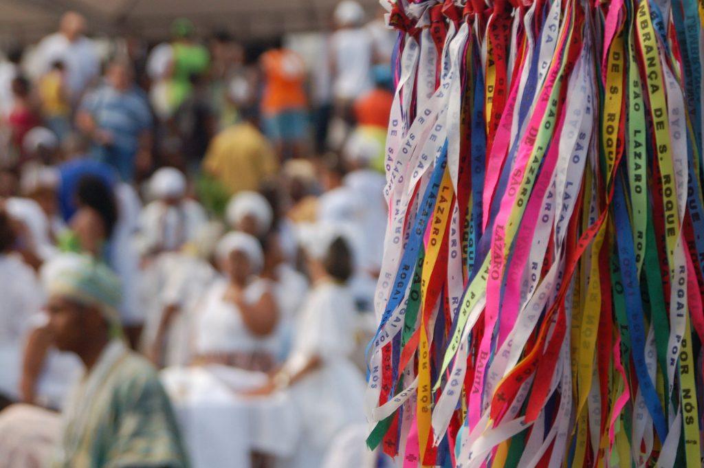 Imagem de um ritual de Candomblé. Várias fitas coloridas e ao fundo mães e pais de santos.