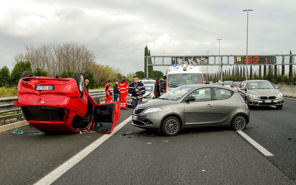 Imagem de um carro vermelho saindo fumaça de ponta cabeça e outro carro prata ao lado todo quebrado.