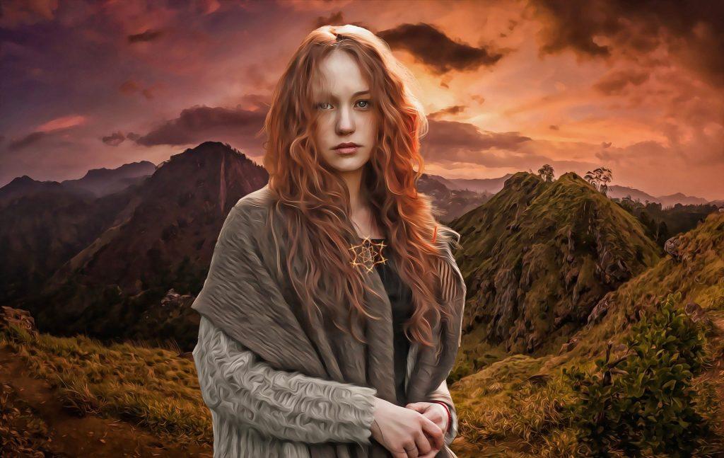 Imagem de uma linda mulher celta. Ela é uma bruxa de cabelos ruivos e longo e que está entre as montanhas.