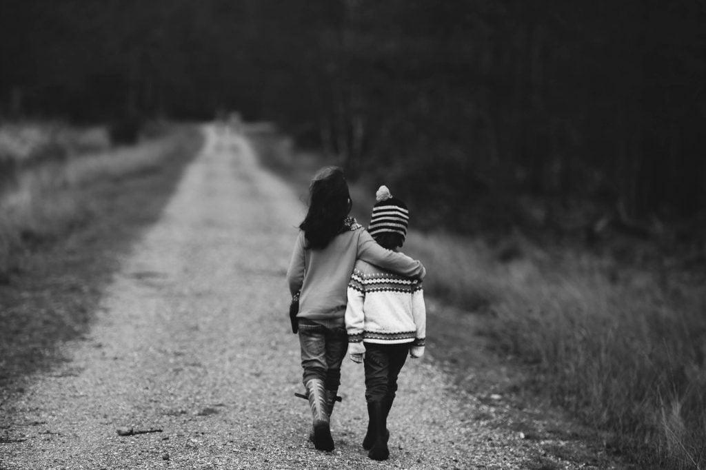 Imagem preto e branco de uma estrada. Nessa estrada duas crianças amigas caminham. A maior abraça a menor. Luto imagem.