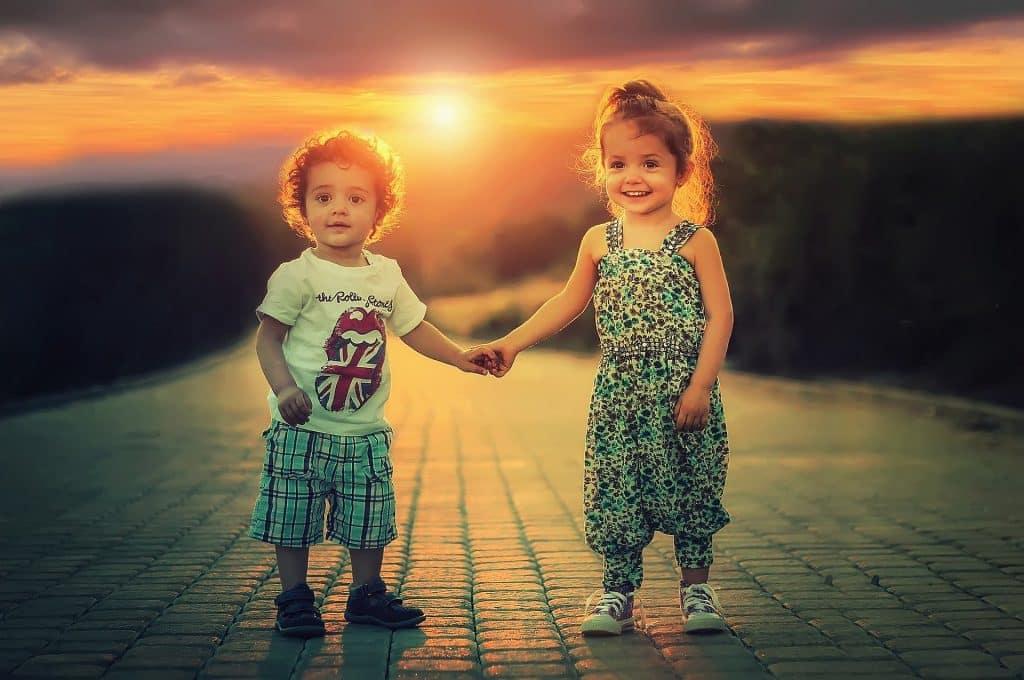 Imagem de duas crianças (um menino e uma menina) sorrindo. Eles estão de mãos dadas e ao fundo o por do sol.
