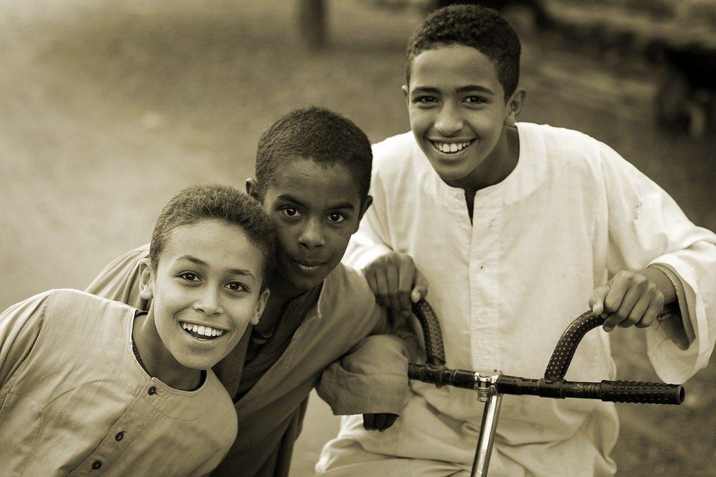 Imagem em preto e branco de três crianças amigas. O maior está sentado em uma bicicleta. Luto imagem.