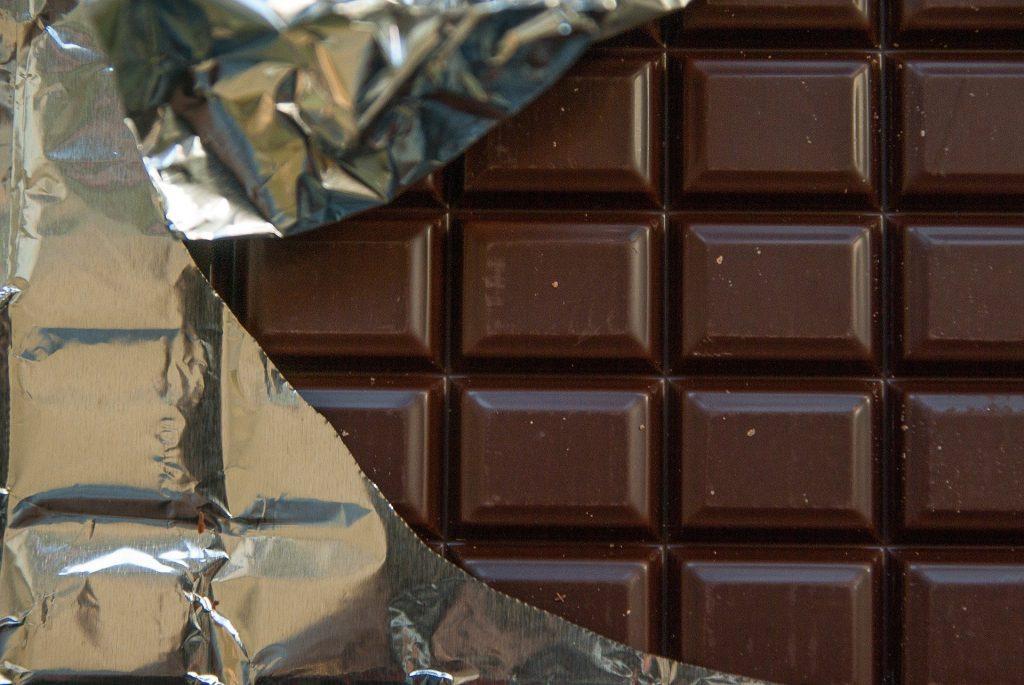 Tablete quadriculado de chocolate amargo. Ele está meio embalado em um papel de alumínio.