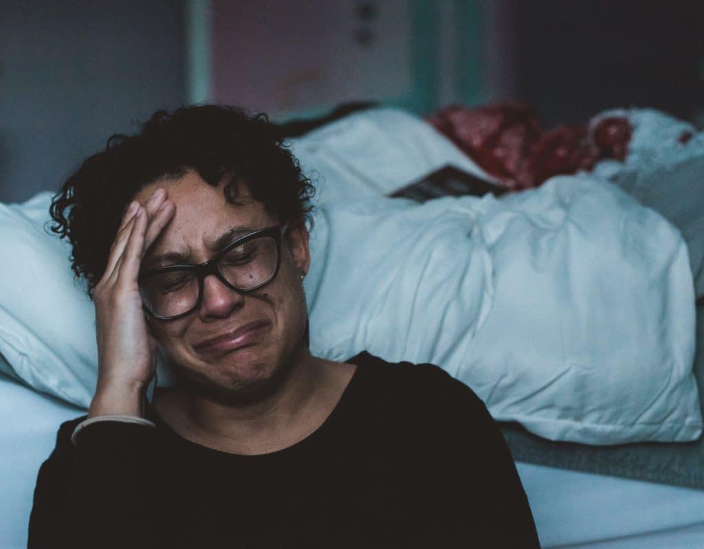 Mulher sentada do lado da cama, no chão, chorando.