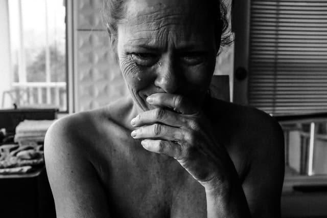 Foto de mulher chorando com mão na boca em preto e branco