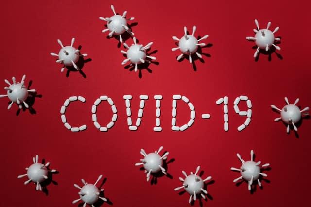 COVID-19 escrito com pílulas em fundo vermelho e itens que parecem vírus em volta